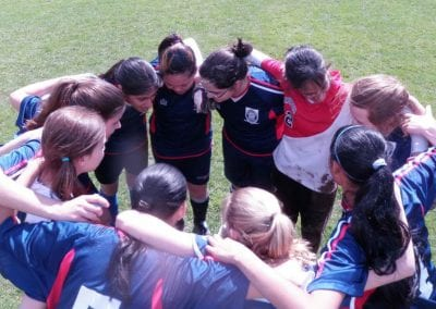 Girls atheletics team in a huddle