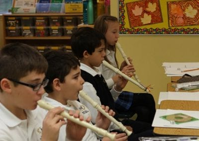 Elementary students practising with recorders