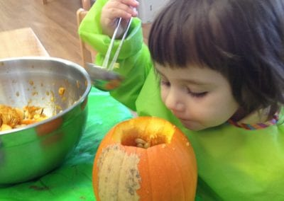 preschooler with pumpkin