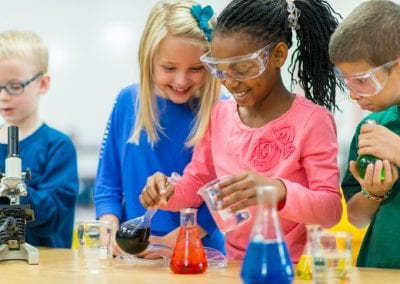 Elementary school students working on science experiments.