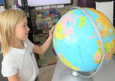 Delta West Academy junior student with globe of the world